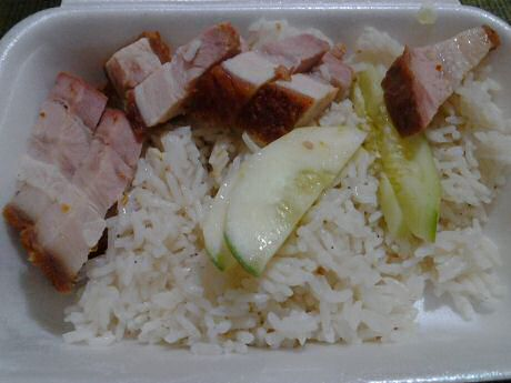Chinese takeaway: roasted pork with cooked rice and slices of fresh cucumber