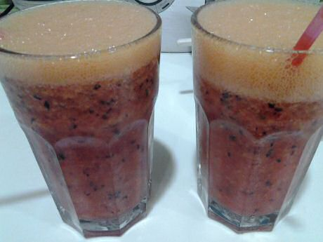 Fruit drink with orange juice, grapes, strawberries and a peach