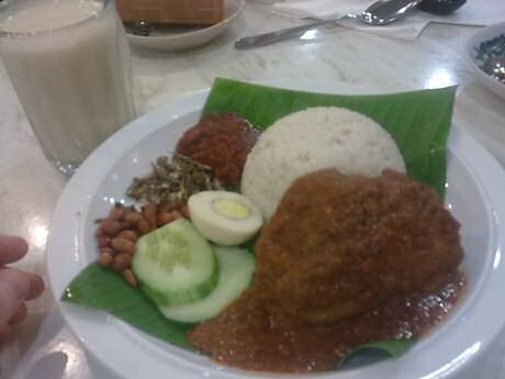 Nasi lemak or Malaysian coconut rice with chicken rendag, cucumber, roasted peanuts, sambal, ikan bilis and soy milk for drinks