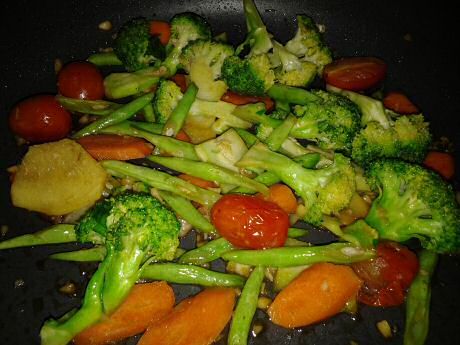Stir fried mixed vegetables: broccoli, carrot and cherry tomatoes with slices of ginger and finely cut garlic